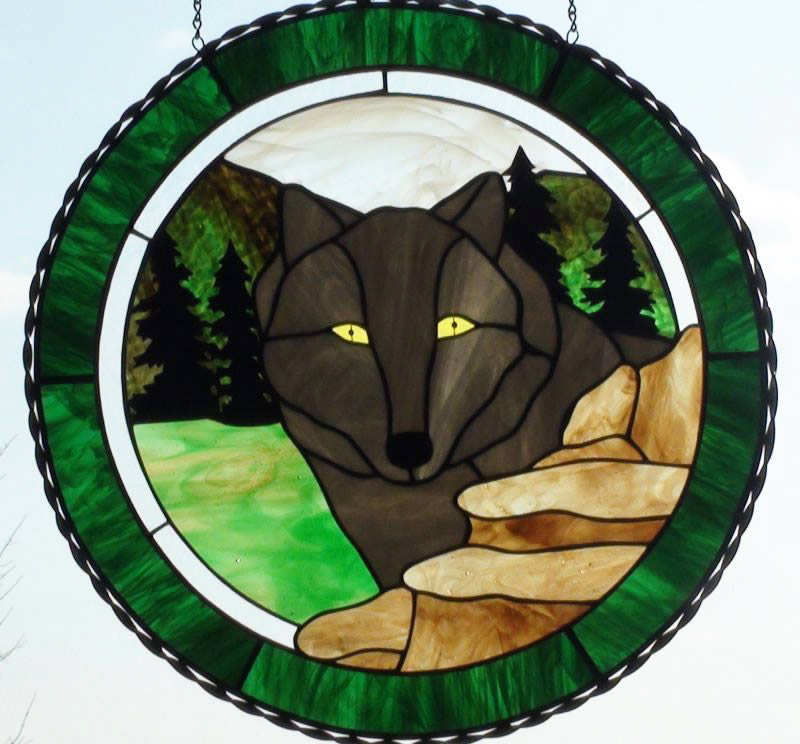 Large window panel designed in a circle as a wolf and wooded background.